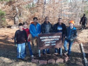 five young men standing behind the WPA Cemetary sign
