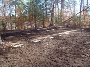 A newly cleaned up row of cemetary headstones laid flat in the ground.