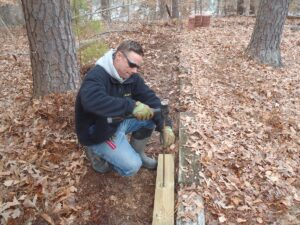 A man pounding a wooden beam into the ground with a mallet